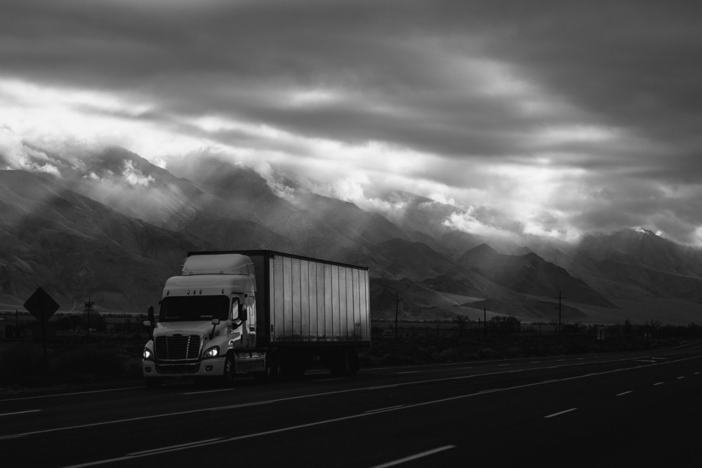 A black and white view of the truck driving on a highway with a mountains behind